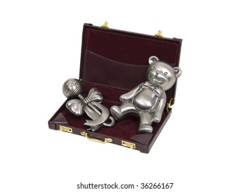 Business inner child shown by pewter baby toys consisting of a rattle and a teddy bear in a briefcase - path included