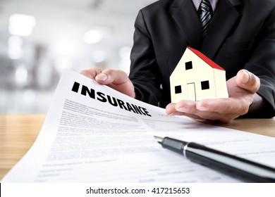 Business Insurance sale man showing an insurance policy and holding house symbol in his hand the policyholder must to sign.