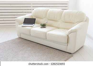 Business and interior concept - view of a white living room with sofa, an open laptop computer, home interior