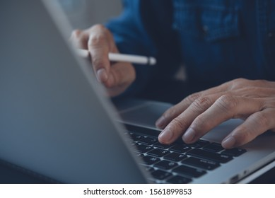 Business, internet technology, social network concept. Close up of business man with stylus pen, hand working, typing on laptop computer keyboard, connecting internet in modern office