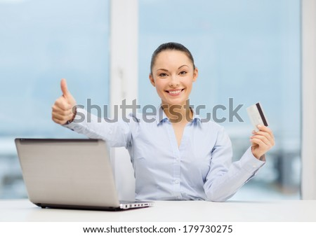 business, investing and technology concept - businesswoman with laptop and credit card in office showing thumbs up