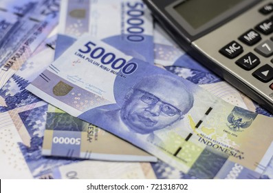 Business and investment with background and texture of new Indonesia rupiah currency,money and calculator,Focus on eye of a man on  banknote