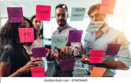 Business investors discussing work looking at the information on sticky notes stuck in office. Colleagues standing in front of post-it notes stuck on glass and discussing.
