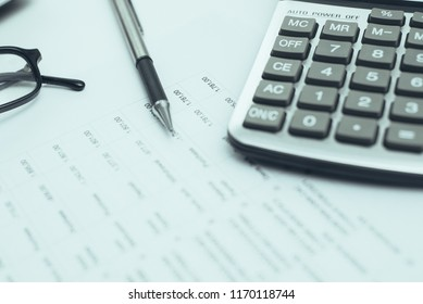 Business items placed on desk. Accountants desk with calculator, ballpoint pen, glasses, laptop and business papers. Paperwork concept