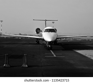 A business jet aircraft parked in the airport terminal unique black and white photo