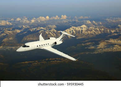 Business jet airplane flying over mountains.