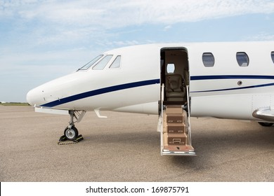 Business jet with open door parked at terminal