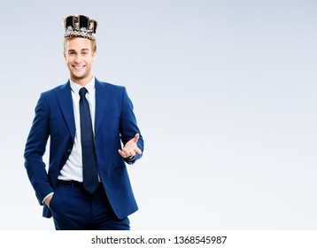I am business king! Bright image of happy smiling young businessman in crown, with copy space for some text, over grey background. Leadership and business success concept.