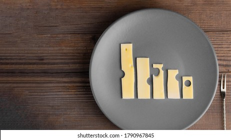Business knockdown and crisis. Food concept. Lowering trend made with cheese graphs on grey plate with fork next to it on wooden table with copy space. Agriculture and dairy manufacture. Top view