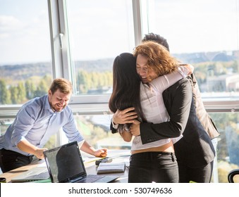 Business ladies hugging showing team work and success of their companies after signing agreement or contract in office interior. Business concept. Teamwork concept.