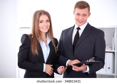 Business lady and businessman standing near each other in white colored office