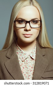 Business lady concept. Portrait of young beautiful blonde girl wearing trendy glasses, casual shirt, jacket and posing over gray background. Close up. Studio shot