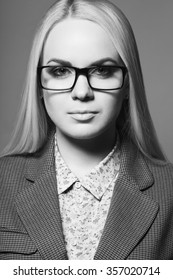 Business lady concept. Portrait of young beautiful blonde girl wearing trendy glasses, casual shirt, jacket and posing over gray background. Close up. Monochrome studio shot