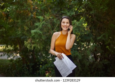 business lady with papers in her hands talking on the phone. The road to work, walk through the park