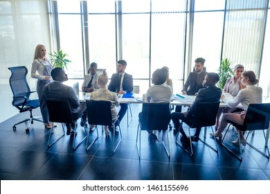 Business lady with positive look and cheerful smile teacher or mentor coach speaking in front of a group of colleagues from different nationalities in a modern office with panoramic windows