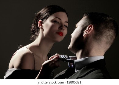 a business lady is pulling man's tie on the black