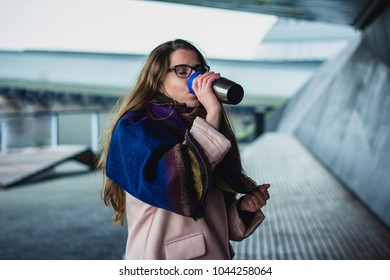 The business lady starts working with a cup of coffee early in the morning on a busy street. She is dressed in a pink coat and scarf, she is in a good mood, and she smiles, looking back