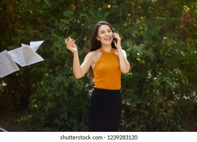 business lady talking on the phone and throwing paper out of her hands. The road to work, walk through the park