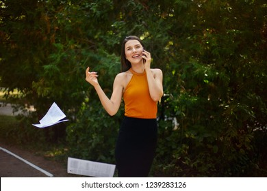 business lady talking on the phone and throwing the paper out of the hands on the way from work. Freedom from paperwork