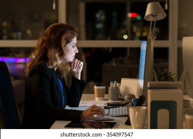 Business lady working on computer in dark office