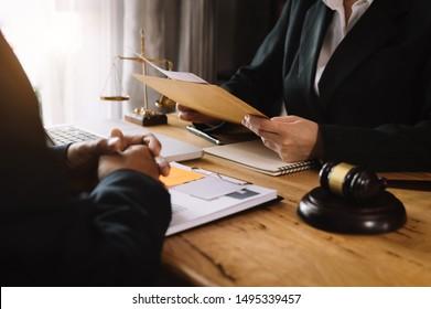 Geschäftsleute und Rechtsanwälte, die auf einem Schreibtisch Vertragsunterlagen mit Messingskala diskutieren. Rechtsberatung, Rechtsberatung, Justiz und Rechtskonzept.