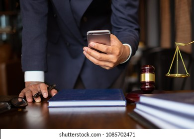 Business lawyers using cell phone for contact customer with brass scale on wooden desk in office. Law, legal services, advice, consult, Justice concept.