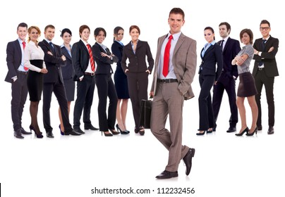 Business leader  with briefcase in his hand, isolated on white . young business man with suitcase looking at  the camera with a large business team behind him