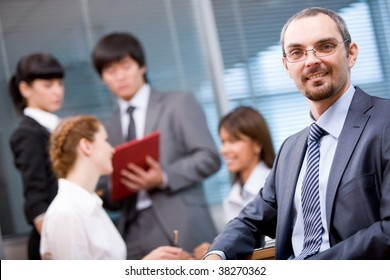 Business leader looking at camera with working team on background