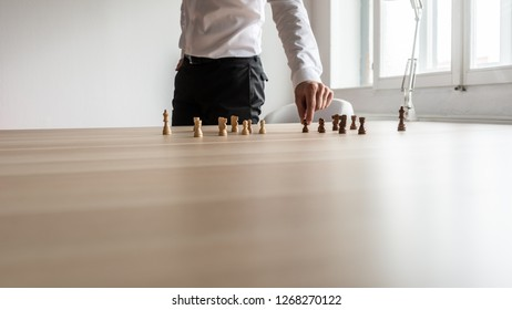 Business leader planning strategy for his company by arranging black and white chess pieces on wooden office desk. With copy space.