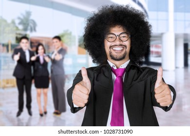 Business leader showing thumbs up in front of his team