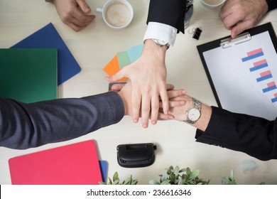 Business leaders joining hands above the table