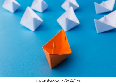 Business Leadership Concept - Yellow Color Paper ship Origami leading the rest of the white paper ship on blue background.