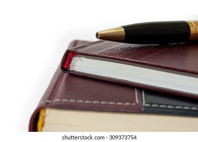 Business leather agendas in a pile with a golden pen.