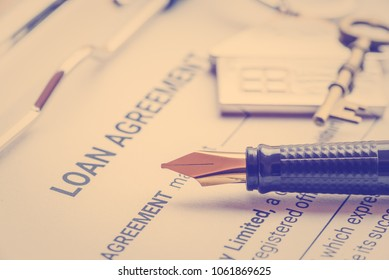 Business legal document concept : Fountain pen and a house key chain on a loan agreement form. Loan agreement is a contract between a borrower and a lender, a compilation of various mutual promises.