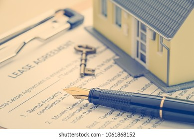 Business legal document concept : Pen, key, a house on a lease agreement form. Lease agreement is a contract between a lessor and a lessee that allow lessee rights to use of a property owned by lessor