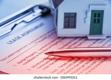 Business legal document concept : Pen and a house on a lease agreement form. Lease agreement is a contract between a lessor and a lessee that allow lessee rights to use of a property owned by lessor.