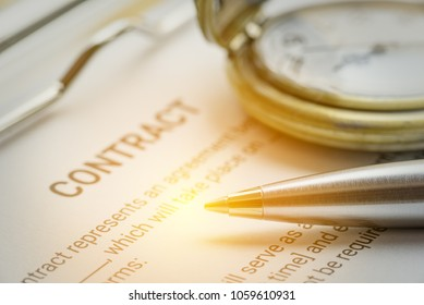 Business legal document, contract / agreement concept : Blue pen, a business contract, a watch on a clipboard. Contract is a branch of the law of obligation in jurisdictions of civil law tradition.