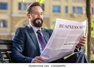 Business life. Cheerful handsome businessman sitting on the bench while reading a daily newspaper