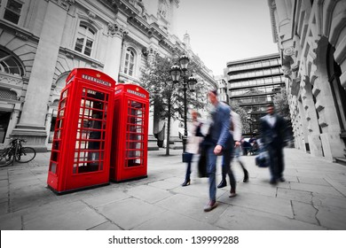 Business life concept in London, the UK. Red phone booth, people in suits walking