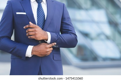 Business Life. Unrecognizable African American Man Adjusting Sleeve Cuff In City. Cropped, Free Space