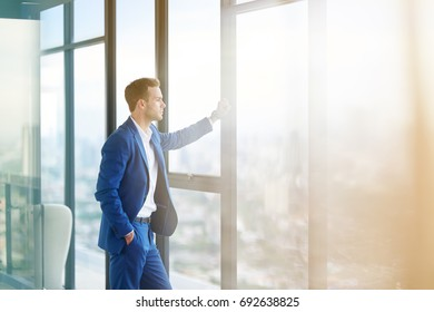 Business lifestyle. Confident professional handsome businessman standing near window in his office while thinking about hos goals