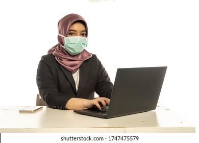 Business Lifestyle, Femme mignonne malaise portant le hijab portant un masque à l'aide d'un ordinateur portable
