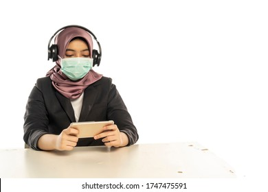 Business Lifestyle, Femme mignonne malaise portant le hijab, portant un masque et un casque, jouant au smartphone