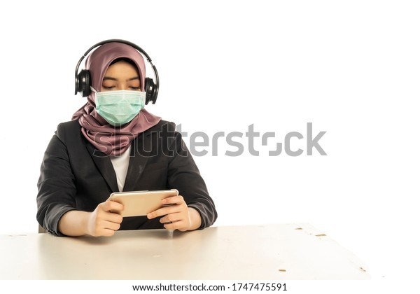 Business Lifestyle, Cute Malay Woman wearing hijab wearing facemask wearing headset playing smartphone