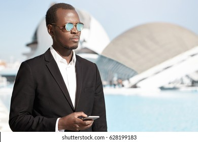 Business, lifestyle, success, career and people. Outdoor portrait of elegant stylish black financier in formal suit and sunglasses using mobile phone, standing against office building background