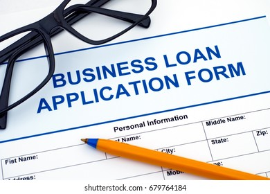 Business Loan Application Form with ballpoint pen and glasses.