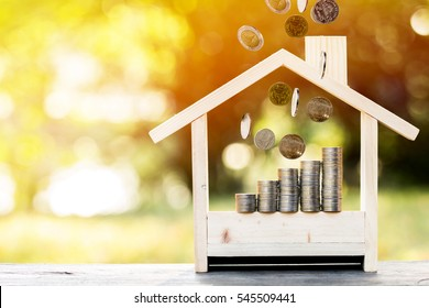 Business loans for real estate concept, a stacking gold coins with growing and dropping put in a model home on bokeh background.