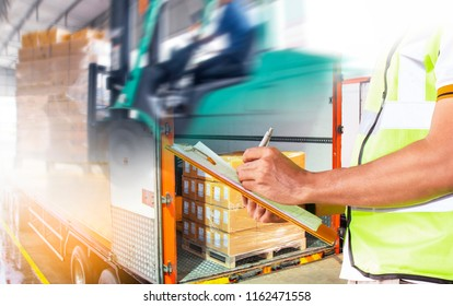 Business Logistic Concept by truck. Blurred driver forklift working in warehouse. Worker are holding clipboard writing with check the shipment pallet loading into a truck.