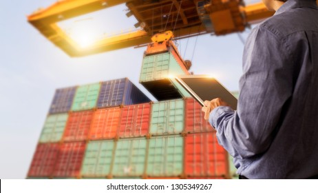 Business Logistics concept, Businessman manager using tablet check and control of Container Cargo ship with working crane bridge. Industry 4.0 concept