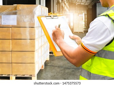business logistics warehouse and transportation, worker man hand holding clipboard with inspecting cargo load into a truck, stack cardboard package boxes or cargo export